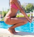 Woman squatting near swim pool outdoors closeup portrait of a Stock Photo