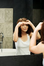 Woman squeeze her acne beautiful in front of the mirror Stock Photos