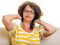 Woman squeezing hair back closed eyes expression curly glasses t shirt isolated on white indoor on sofa Royalty Free Stock Image