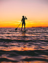 Woman stand up paddle boarding at dusk on a flat warm quiet sea with beautiful sunset colors Royalty Free Stock Photo
