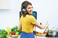 Woman standing back in kitchen cooking healthy food with fun a and listen music headphones Royalty Free Stock Images
