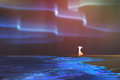 Woman standing on beach glows with Northern lights Aurora borealis above Royalty Free Stock Photo