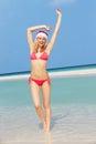 Woman standing on beach wearing santa hat smiling Royalty Free Stock Image