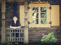 Woman standing close old cottage middle aged window Royalty Free Stock Image
