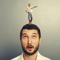 Woman standing on the head of amazed man Stock Images