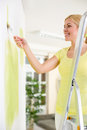 Woman standing on a ladder and painting white wall with vibrant yellow paint using roller as she redecorates her house Stock Image