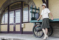 Woman standing and leaning against an old retro luggage cart by train station entry door. Royalty Free Stock Photo