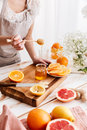 Woman standing near table with citruses and holding honey. Royalty Free Stock Photo