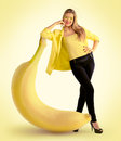 Woman standing next to a large banana concept Stock Photography
