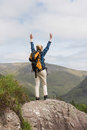Woman standing on rock cheering after a hike in majestic mountain scenery Royalty Free Stock Images