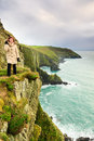 Woman standing on rock cliff by the ocean co cork ireland irish atlantic coast tourist europe beautiful sea landscape natures Stock Photography