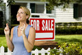 Woman standing by a for sale sign outside a family house fingers crossed Stock Photo