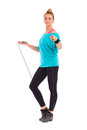 Woman standing with skipping rope young female full length studio shot isolated on white Stock Photography