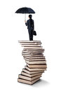 Woman standing on a stack of books young businesswoman with umbrella Stock Image