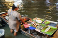 Woman standing in water is cooking seafood for tourists on floating market. Bangkok, Thailand. Royalty Free Stock Photo
