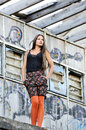 A woman standing young fashionable next to an abandoned building Stock Photos