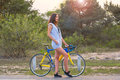 Woman stands with a bicycle on a road in the park in the sunset Royalty Free Stock Photo