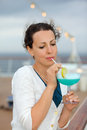 Woman stands and drinks blue cocktail Royalty Free Stock Photo