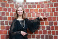 A woman stands near the brick wall in black dress Royalty Free Stock Photo