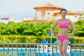Woman stands near to handrails at poolside young smiling with hands akimbo Stock Photo