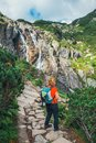Woman stands on the cliff and looks at the tops