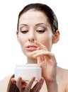 Woman starting to apply face cream holding container and isolated on white Stock Image