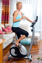 Woman on stationary bicycle Royalty Free Stock Photos