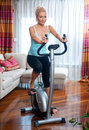 Woman on stationary bicycle Stock Photography