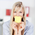 Woman with sticky note portrait of a covering her mouth using a yellow empty Stock Photography