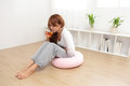 Woman with stomach ache portrait of sitting on floor at home asian model Stock Photography