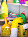 Woman storing cleaning tools in pantry with safety gloves cleaners storage place high on the wall house and supplies concept Stock Photo