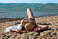 Woman in straw hat lying on the beach Royalty Free Stock Photos