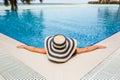 Young woman in bikini wearing a straw hat by the swimming pool