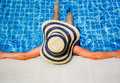 Woman with hat in swimming pool