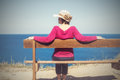 Woman in a straw hat sits on a bench by the sea Royalty Free Stock Photo