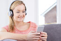 Woman Streams Music From Mobile Phone To Wireless Headphones Royalty Free Stock Photo