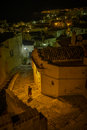Woman in the streets of matera walking under a street light old italy Stock Photos