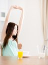 Woman stretches herself sitting at the kitchen table with breakfast and glass of orange juice Royalty Free Stock Photo