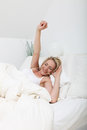 Woman stretching against her pillows Stock Photos