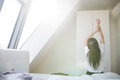 Woman stretching in bed after wake up in morning with sunlight Royalty Free Stock Photo