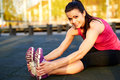 stock image of  Woman stretching hamstrings and smiling.