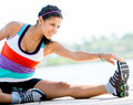 Woman stretching her leg before workout outdoors Royalty Free Stock Photos