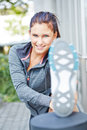 Woman stretching her legs in the city smiling athletic Stock Photos