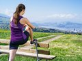 Woman stretching her legs in the park photo of a young leg before she starts to run on a country path city and lake distance Stock Image