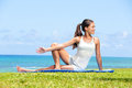 Woman stretching legs in yoga exercise fitness training outside by the ocean sea beautiful fit female girl model sitting on grass Royalty Free Stock Photography