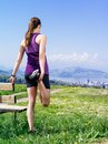 Woman stretching in the park photo of a young her leg before she starts to run on a country path city and lake distance Royalty Free Stock Photos