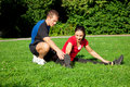 Woman stretching with personal trainer outdoors Royalty Free Stock Photo