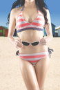 Woman in striped bikini holds sunglasses Royalty Free Stock Photo