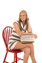 Woman striped dress stack books sit side a sitting in a chair holding on to a of Royalty Free Stock Photography