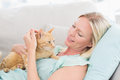 Woman stroking cat while lying on sofa Royalty Free Stock Photo